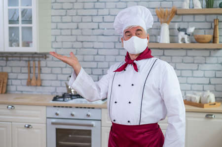 Male elderly chef in a medical mask in a restaurant kitchen Banque d'images