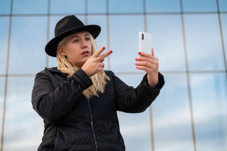 Deaf-mute young woman and speaks sign language over video communication on the phone outdoors