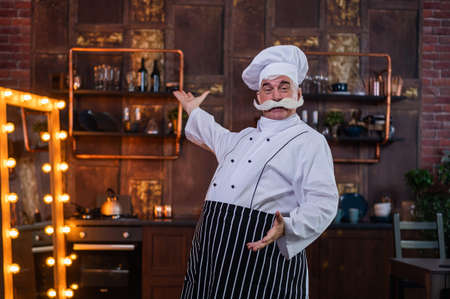 An elderly male chef straightening his thick gray mustache while standing in the kitchen