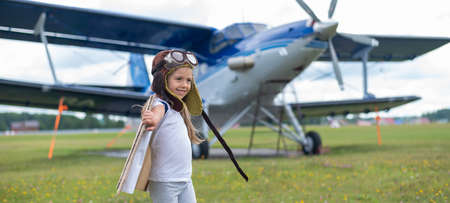 A little girl plays a pilot on the background of a small plane with a propeller. A child in a suit with cardboard wings dreams of flying Banque d'images