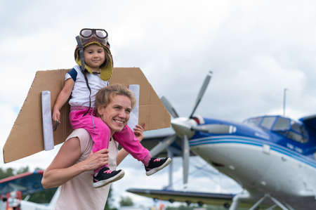 A Caucasian woman and her little daughter are playing a pilot against the backdrop of a small plane with a propeller Banque d'images