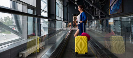 Caucasian woman on a horizontal escalator with a suitcase at the airport. A girl with pink luggage rides on a moving sidewalk