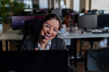 Smiling woman in headset talking to customer. Female worker of call center