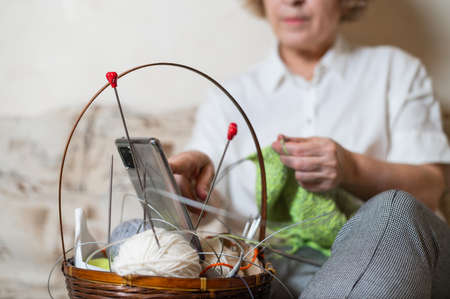 Faceless old woman knits and watches online training on a smartphone. Close-up of female hands with yarn and knitting needles. Banque d'images