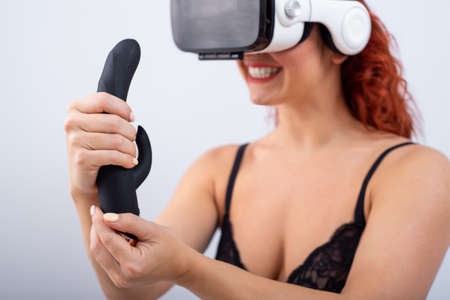 Woman in virtual reality glasses holding black dildo on white background.