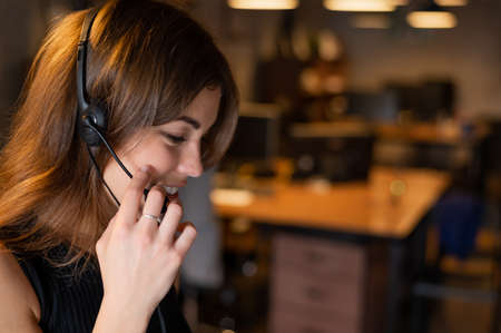 Portrait of a beautiful smiling woman call center operator with a headset at the desk