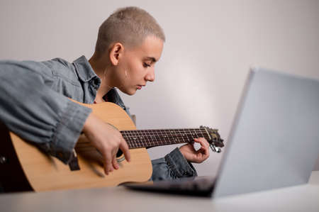 Young caucasian woman with short blonde hair playing guitar and watching training video on laptop. 写真素材