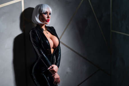 Sexy woman in a blonde wig and latex catsuit.