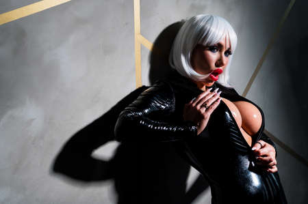 Sexy woman in a blonde wig and latex catsuit. Standard-Bild