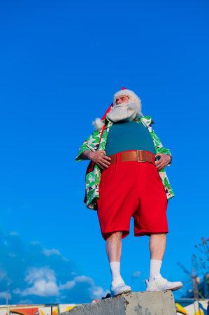 Santa claus in a hawaiian shirt on a blue sky background. Stockfoto
