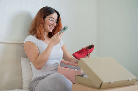 The woman unpacks the delivered shoes. The girl leaves a review about the order in the application on the smartphone