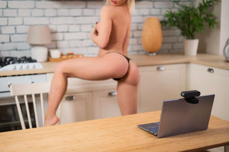 A girl in underwear flirts on an online video connection on a laptop. Woman working as a web cam model Banque d'images
