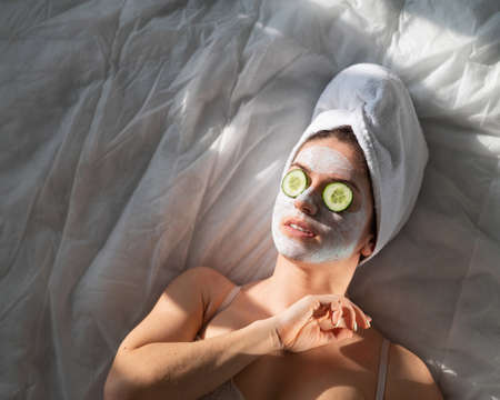 A woman with a towel on her hair and in a clay face mask and cucumbers in front of her eyes lies on the sheet 写真素材