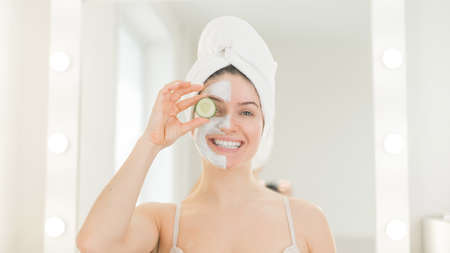 Cheerful woman with a towel on her hair and in a clay face mask fooling around with cucumbers in her hands. Taking care of beauty at home