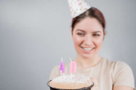 The happy woman makes a wish and blows out the candles on the 40th birthday cake. Girl celebrating birthday. Copy space.