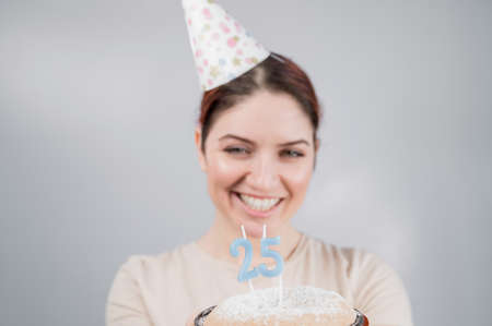 The happy woman makes a wish and blows out the candles on the 25th birthday cake. Girl celebrating birthday.