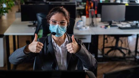 Caucasian woman in medical mask showing thumbs up in office.