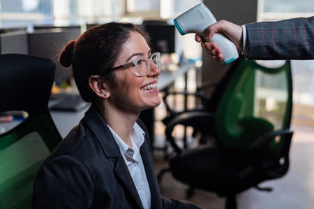 Smiling business woman has body temperature measured with electronic thermometer at workplace in office.