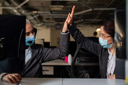 Two business women in masks are giving a high five while sitting at one desk in the office