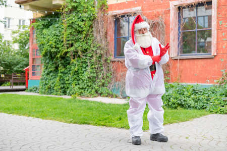 Santa claus in a protective costume puts on gloves.