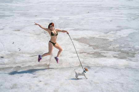 A woman in a bikini walks with a dog in the snow