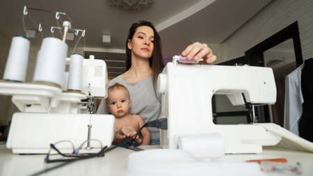 Young woman sews at home and holds a small child. Mom teaches her little son to sew on a sewing machine 写真素材