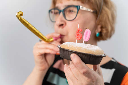 Happy caucasian woman celebrating 60 years birthday and blowing a whistle in tongue on white background.