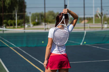 Woman in skirt standing back on the tennis court and holds the racket.