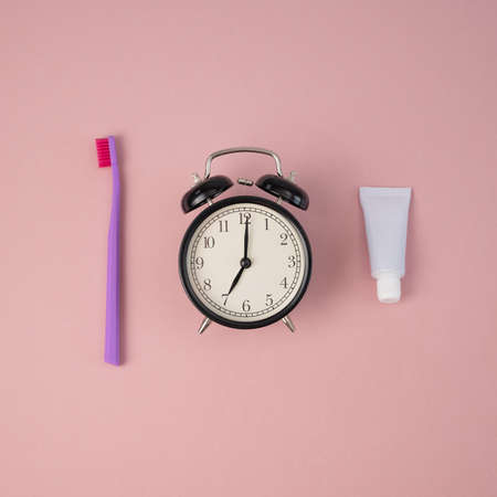 Toothbrush, tube of toothpaste and alarm clock on a pink background. Time to brush your teeth. 写真素材