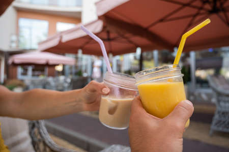 A man and a woman clink glasses of soft drinks in an outdoor cafe. Close-up of hands of a couple on a date