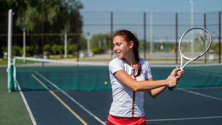 Young caucasian woman playing tennis on an outdoor court on a hot summer day.