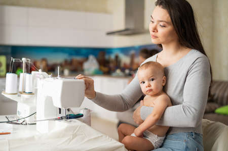 Young woman sews at home and holds a small child. Mom teaches her little son to sew on a sewing machine. Self-isolation homework