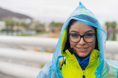 Portrait of a smiling woman with glasses wearing a raincoat outdoors. 写真素材