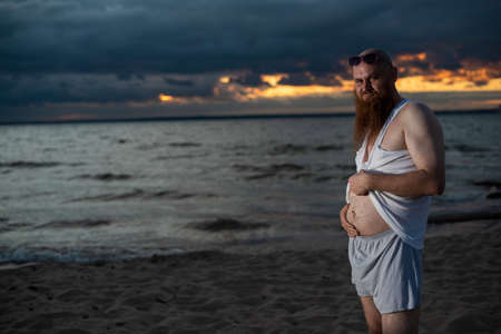 Humorous portrait of a brutal man posing on the beach at sunset