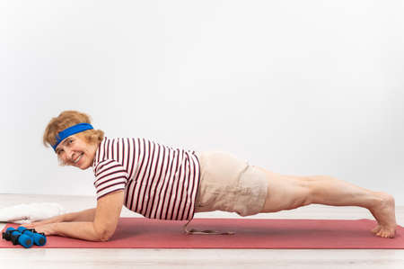 A happy old woman doing a plank on a sports mat. Elderly lady doing fitness exercises on white background.