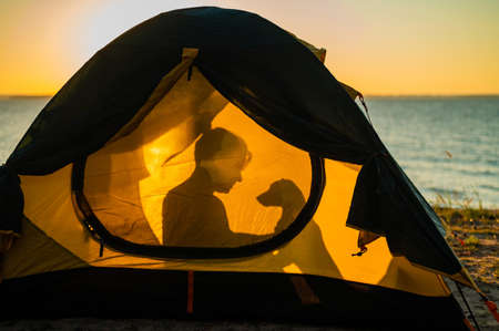 Woman and dog in a tourist tent at sunset. Camping with a pet