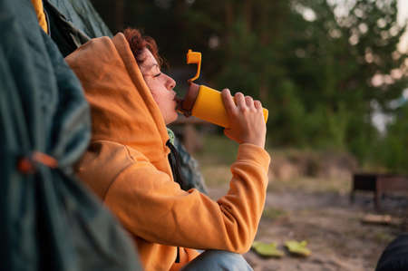 A pensive Caucasian woman in a sweatshirt sits in a tourist tent and drinks from a mug  . Rest at nature. 写真素材