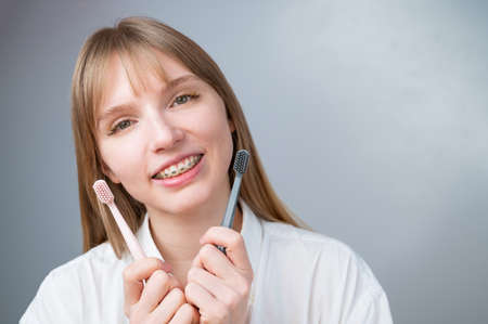 Caucasian woman in braces holding toothbrushes on white background.