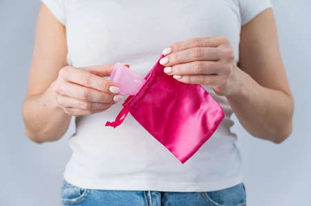 A faceless Caucasian woman in underpants puts a pink menstrual cup in a small silk bag. Eco Friendly Products: Feminine intimate hygiene during menstruation