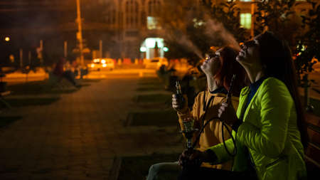 Two caucasian women smoke vape and hookah outdoors at night. 写真素材
