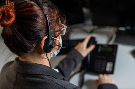 Rear view of a woman working in the office wearing a medical mask. Female call center operator wearing a protective mask.