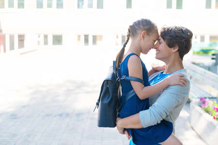 A loving mother is holding her daughter. Caucasian woman hugs a schoolgirl