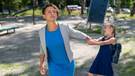 The naughty girl pulls her mother by the hand, wanting to stay on the playground. The capricious daughter resists and does not want to leave.