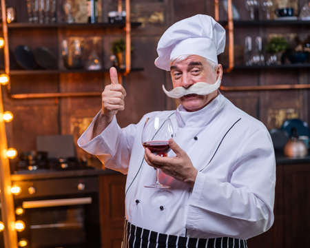Portrait of friendly elderly male professional sommelier wearing apron and hat tasting red wine.