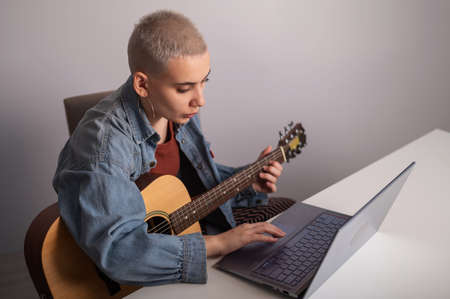 Young woman is learning to play the guitar online. Remote music lessons on a laptop 写真素材
