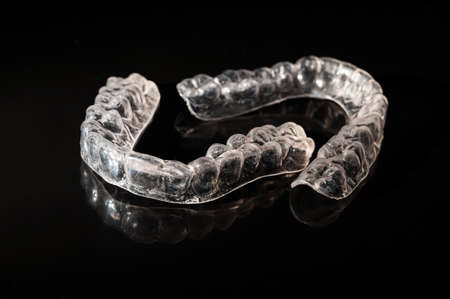 Removable plastic retainers for bite correction on a black background
