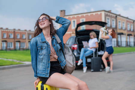 Three girlfriends go on a road trip. Young woman posing with a suitcase. Two girls are sitting on the trunk of a car and watching a map.