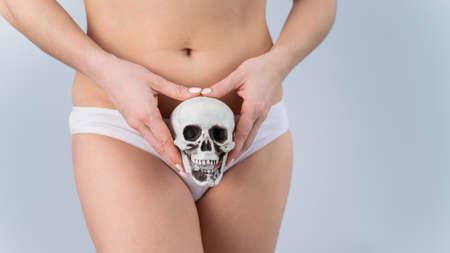 Faceless woman in underpants holding a skull on a white background. 写真素材