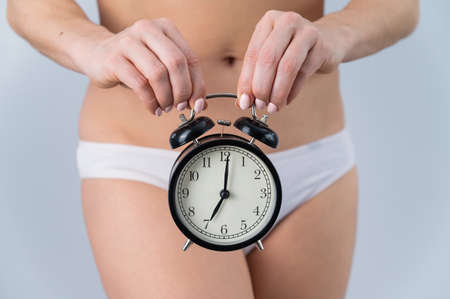 A faceless woman in shorts holds an alarm clock on a white background. Female biological clock concept
