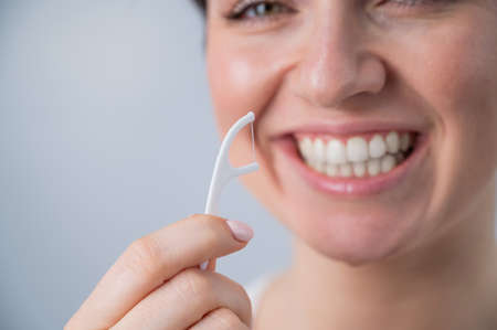 Close-up portrait of a beautiful caucasian woman with a flawless smile holding a toothpick with dental floss on a white background 写真素材